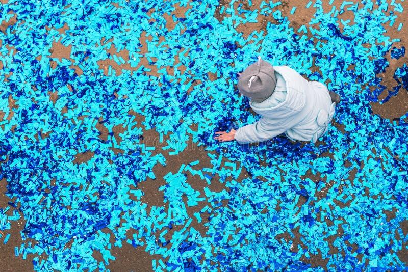 Uma menina em um chapéu e em um revestimento no asfalto recolhe confetes Brincadeiras com uma serpentina após um feriado, anivers imagem de stock