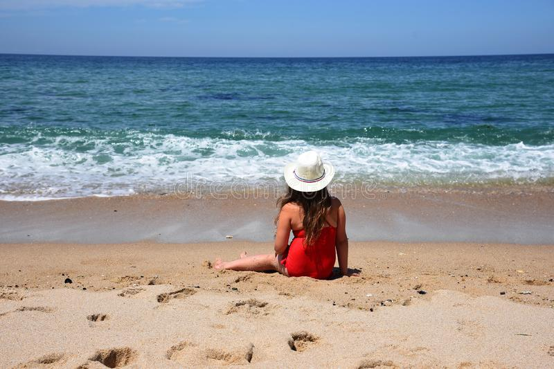 Uma menina em um maiô vermelho admira o oceano porto portugal foto de stock