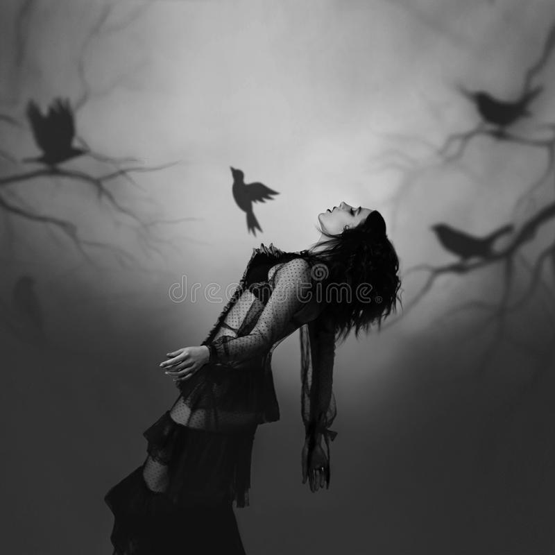 Uma menina em um preto, vestido do vintage que levanta na perspectiva de uma floresta sombrio, que seja criada pelo projetor imagens de stock