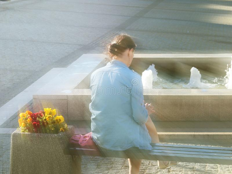 Uma menina em um revestimento azul da sarja de Nimes senta-se em um banco perto da fonte e olha-se o telefone celular Paisagem da imagens de stock