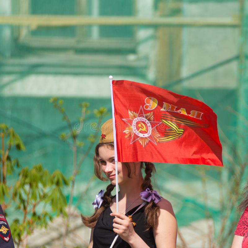 Uma menina em um tampão de campo com uma bandeira vermelha na ação imagem de stock royalty free