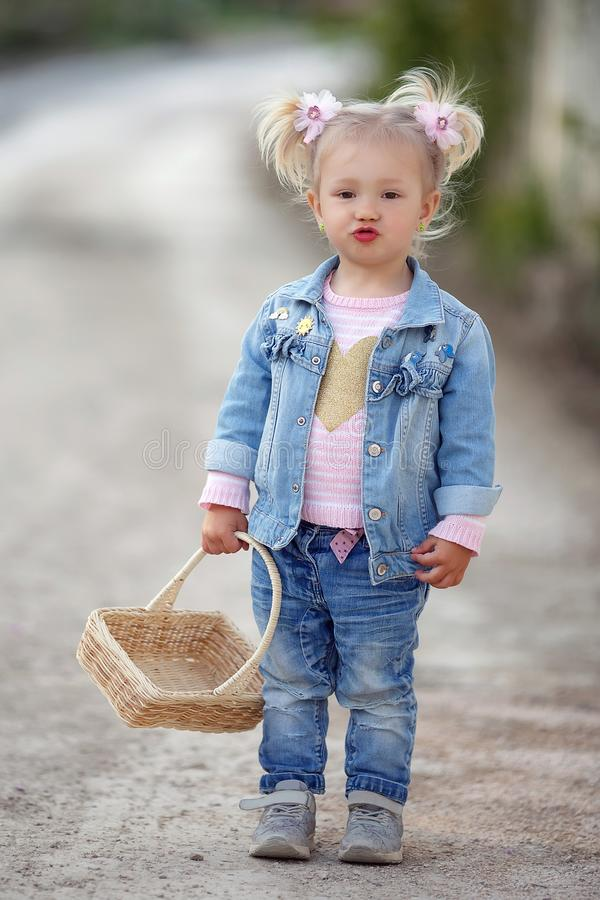 Uma menina em um terno da sarja de Nimes anda apenas em um parque da mola com uma cesta de vime em suas mãos fotos de stock royalty free