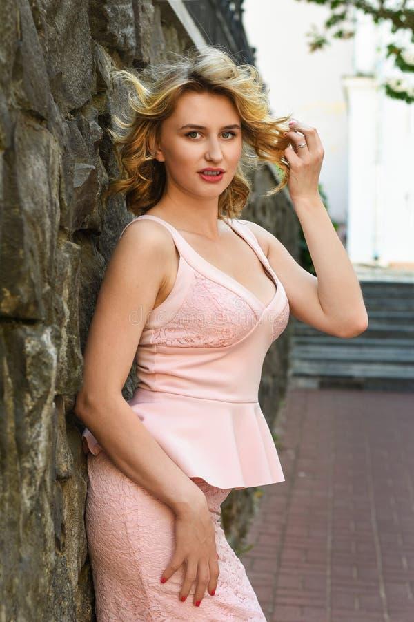 Uma menina em um terno elegante está perto de uma parede na cidade velha imagem de stock