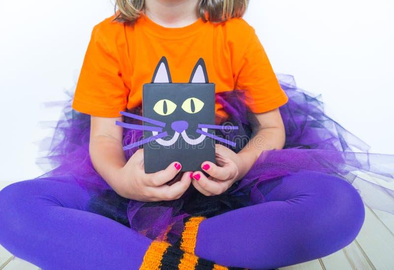 Uma menina em um traje da bruxa guarda um gato preto fotografia de stock