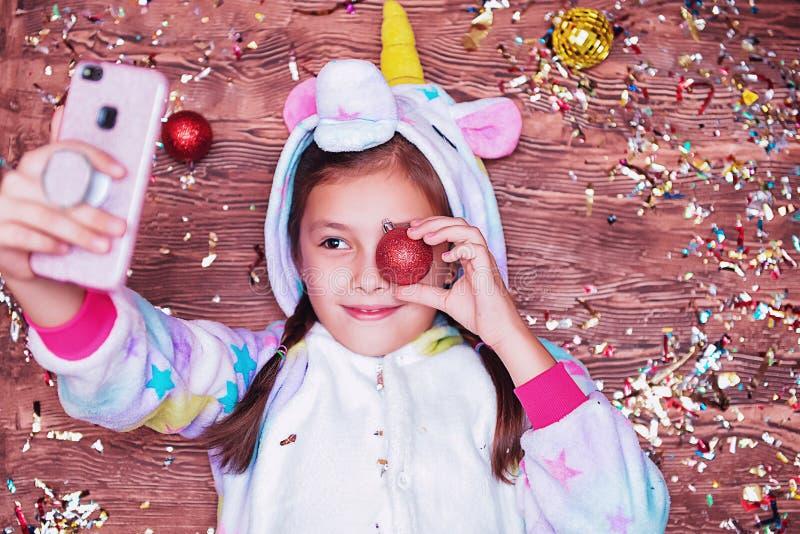 Uma menina em um traje do unicórnio Conceito do Natal Menina que encontra-se em um fundo de madeira, muito confete colorido A men foto de stock royalty free