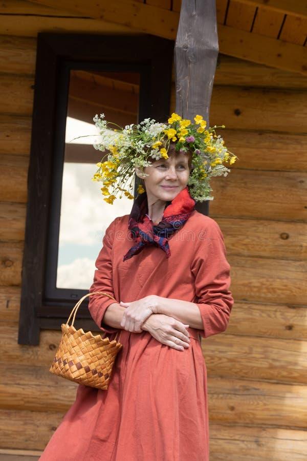 Uma menina em um traje nacional e em uma grinalda em sua cabeça recolhe bagas em uma cesta, em um gramado verde dentro fotografia de stock