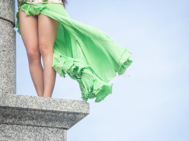 Uma menina em um verde, vestido do cal para poses da dan?a de barriga em uma coluna de m?rmore imagens de stock