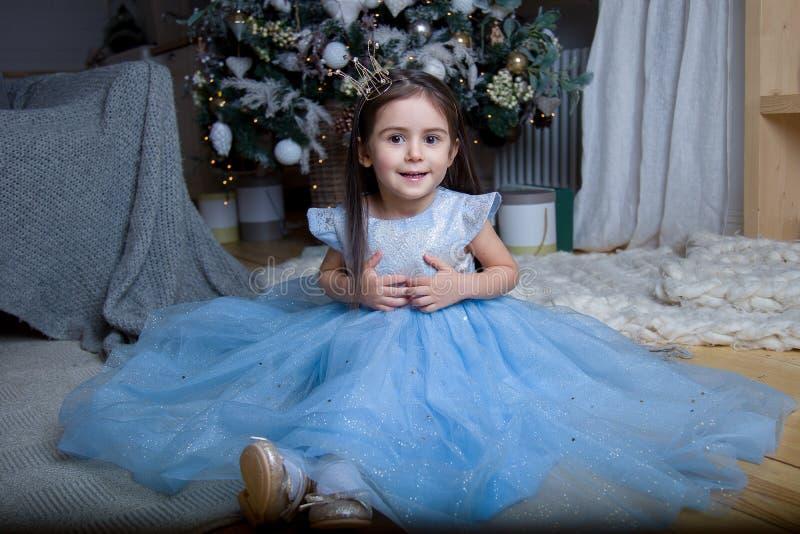Uma menina em um vestido azul bonito na árvore de Natal imagens de stock royalty free