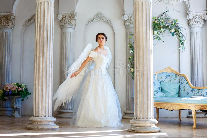 Uma menina em um vestido bonito e em umas asas brancas de um anjo inspira imagens de stock royalty free