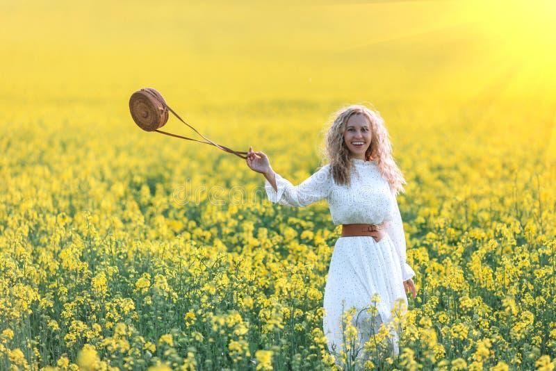 Uma menina em um vestido branco longo que admira o alvorecer ou o por do sol no campo amarelo brilhante foto de stock