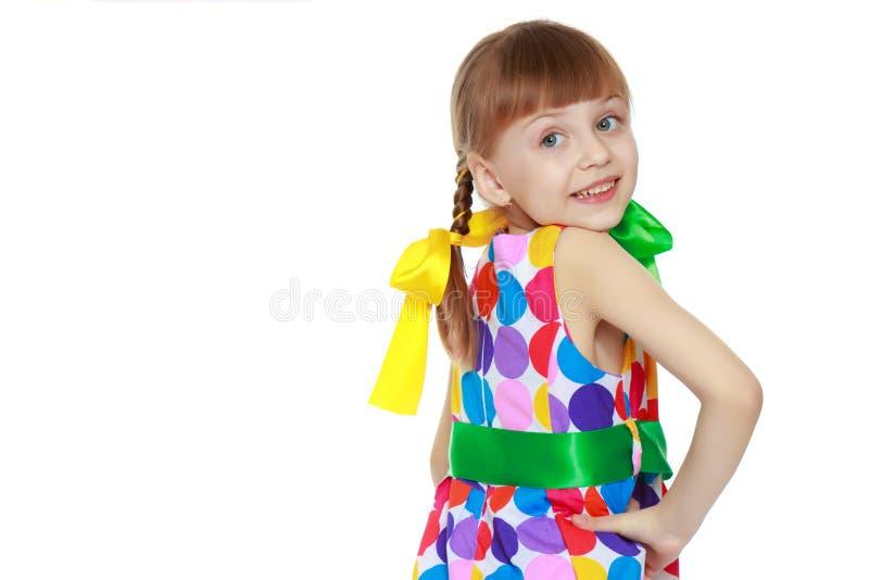 Uma menina em um vestido com um teste padr?o do circl multi-colorido imagens de stock royalty free