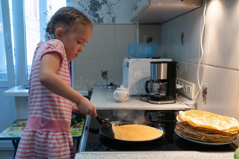Uma menina em um vestido cor-de-rosa está fritando panquecas em um fogão elétrico fotos de stock