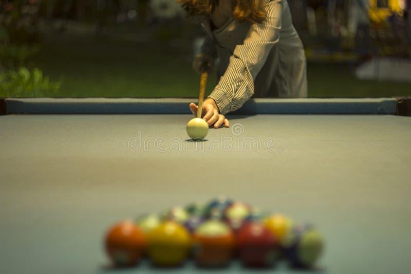 Uma menina em um vestido listrado guarda uma sugestão sobre uma mesa de bilhar com pano azul e as bolas de bilhar borradas fotos de stock