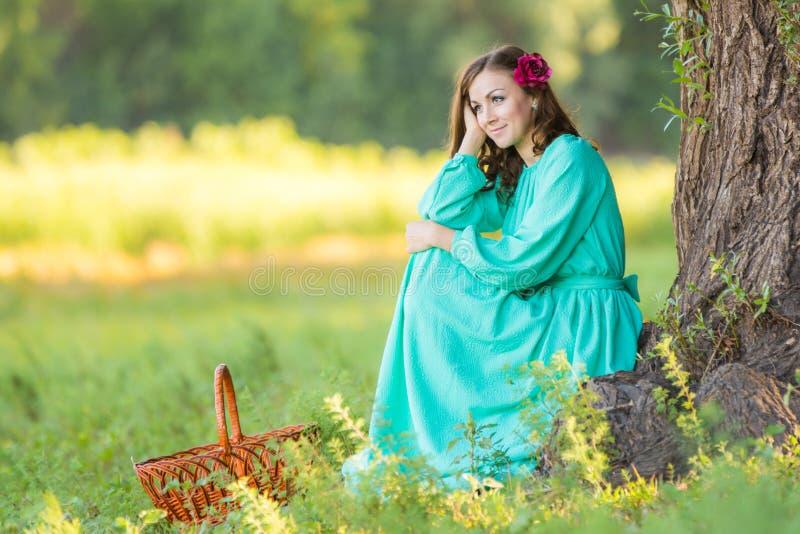 Uma menina em um vestido longo e sentada para baixo no pensamento de uma árvore velha na floresta fotos de stock