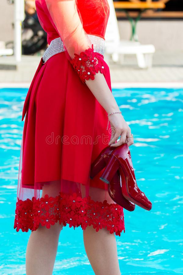 Uma menina em um vestido vermelho e em sapatas em suas caminhadas da mão perto da associação Férias de verão no recurso com um po imagem de stock royalty free