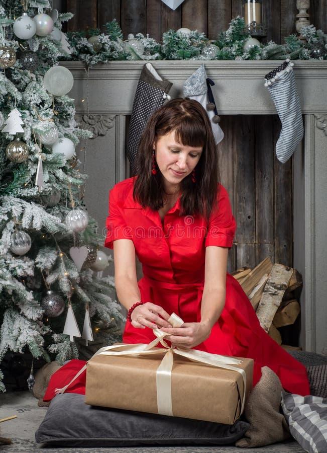 Uma menina em um vestido vermelho envolve um presente de Natal em uma grande caixa e põe-nos sob uma árvore de Natal imagens de stock royalty free