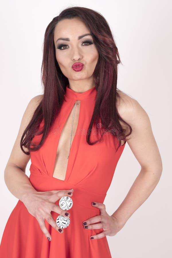 Uma menina em um vestido vermelho que guarda bolas do loto foto de stock
