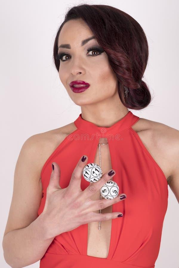 Uma menina em um vestido vermelho que guarda bolas do loto imagem de stock