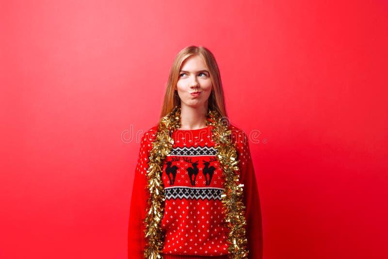 Uma menina emocional em uma camiseta do Natal e com ouropel em seu pescoço, com uma expressão astuto, pensamento sobre algo, isol imagens de stock royalty free