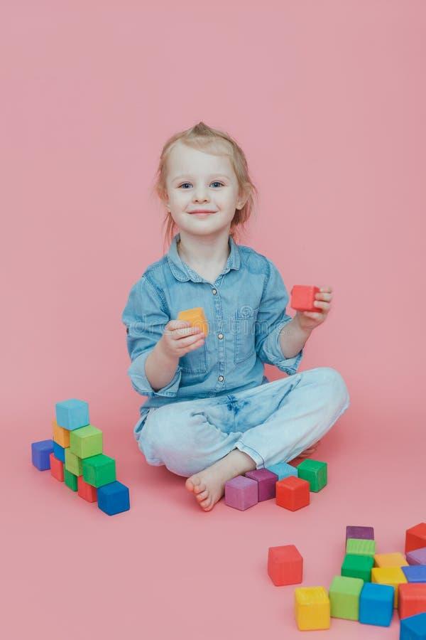 Uma menina encantador na roupa da sarja de Nimes em um fundo cor-de-rosa joga com os cubos coloridos de madeira fotos de stock royalty free