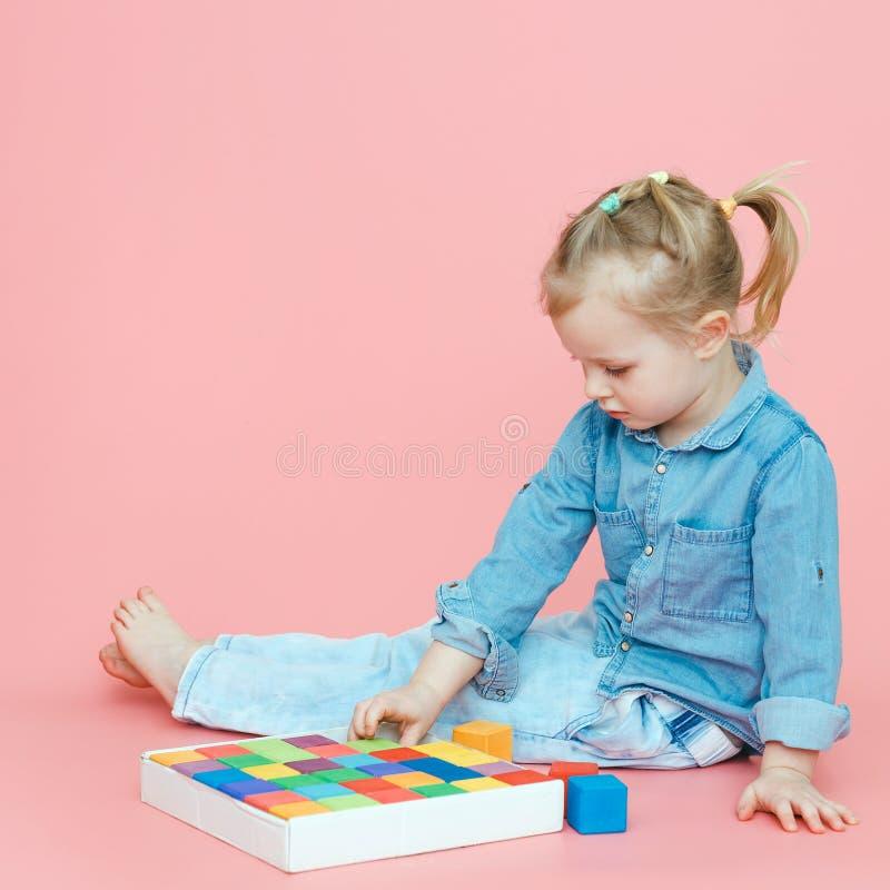 Uma menina encantador na roupa da sarja de Nimes em um fundo cor-de-rosa põe cubos multi-coloridos de madeira em uma caixa branca imagens de stock