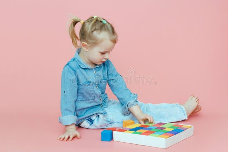 Uma menina encantador na roupa da sarja de Nimes está encontrando-se em um fundo cor-de-rosa entre cubos coloridos de madeira e r fotos de stock