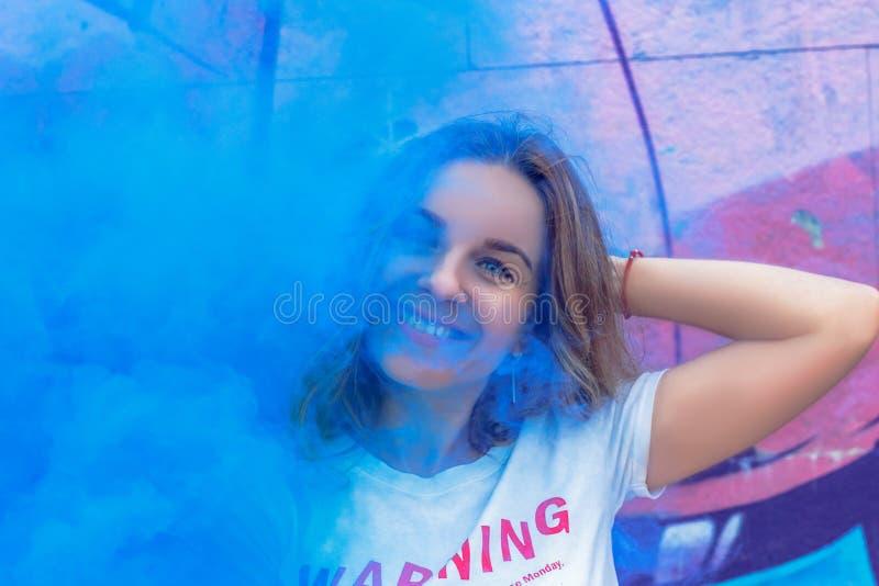 Uma menina encantador no fumo colorido contra o fundo dos grafittis imagem de stock