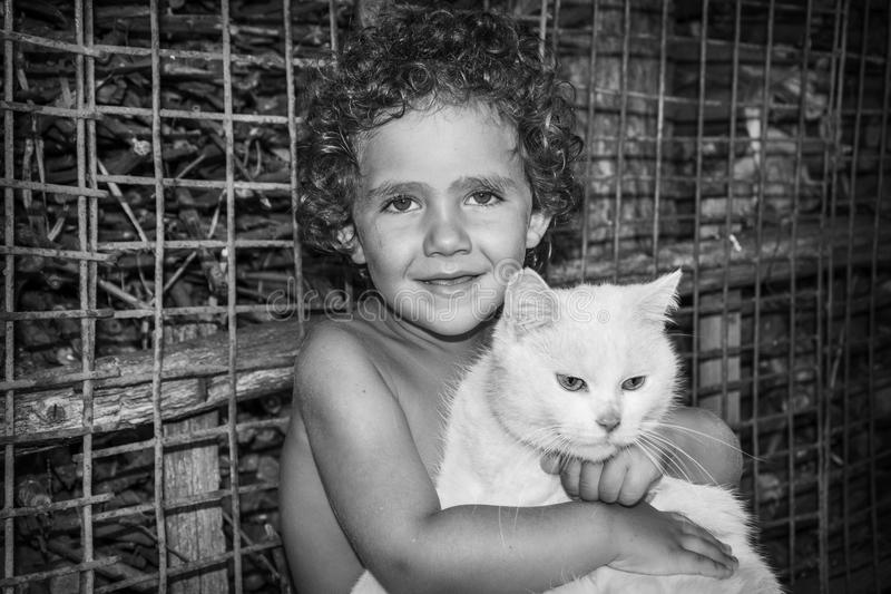 Uma menina encaracolado pequena está guardando um gato branco Phot preto e branco foto de stock