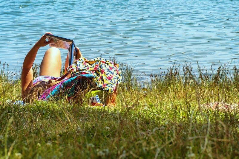 Uma menina encontra-se em um rio e l?-se um livro Jovem mulher que l? um livro ao sentar-se pelo rio fotos de stock royalty free