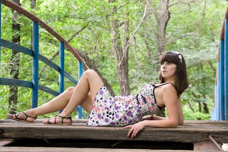 Uma menina encontra-se em uma ponte fotos de stock
