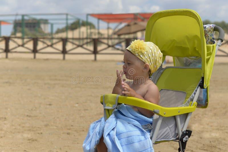 Uma menina engraçada pequena que senta-se em uma cadeira de rodas na costa arenosa fotos de stock royalty free