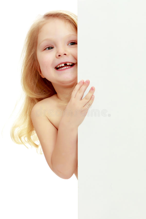 Uma menina espreita para fora atrás da bandeira imagens de stock royalty free