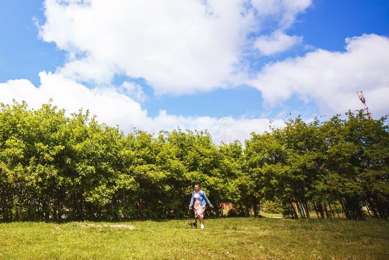 Uma menina está andando com um cão Yorkshire terrier fotografia de stock royalty free