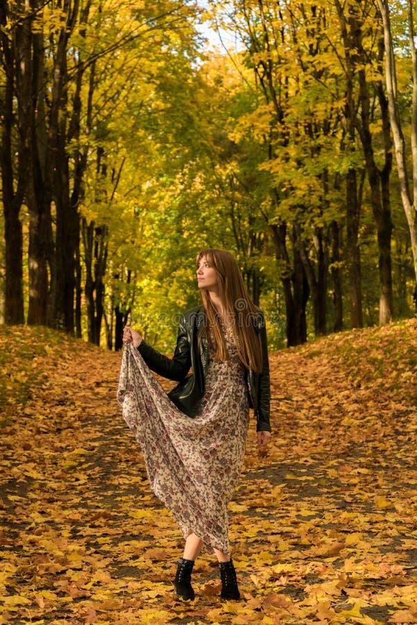 Uma menina está andando em um parque do outono imagens de stock