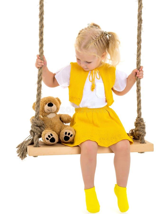 Uma menina está balançando em um balanço com um urso de peluche fotografia de stock