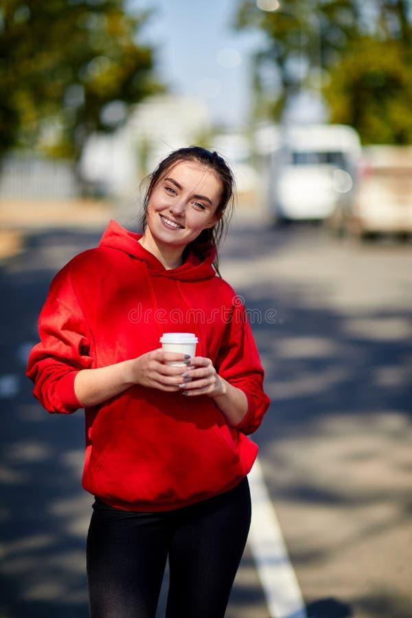 Uma menina está de sorriso com uma xícara de café em um fundo borrado fotos de stock royalty free