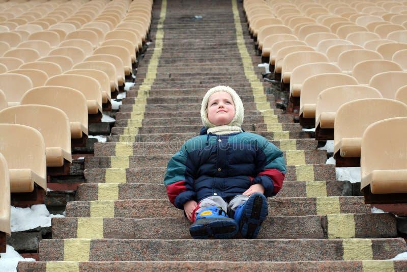 Uma menina está em escadas na zona vazia para fãs no estádio imagem de stock royalty free