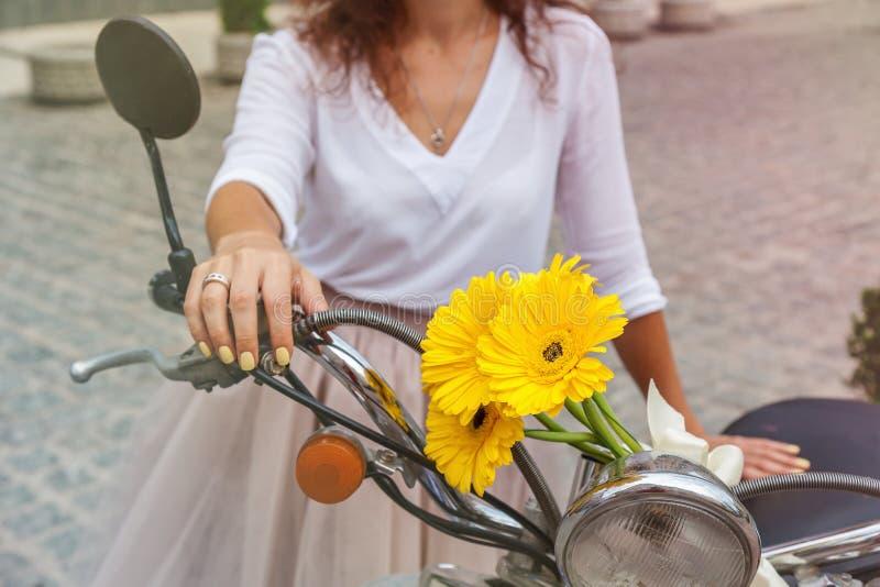 Uma menina está estando perto de uma bicicleta motorizada fotos de stock royalty free