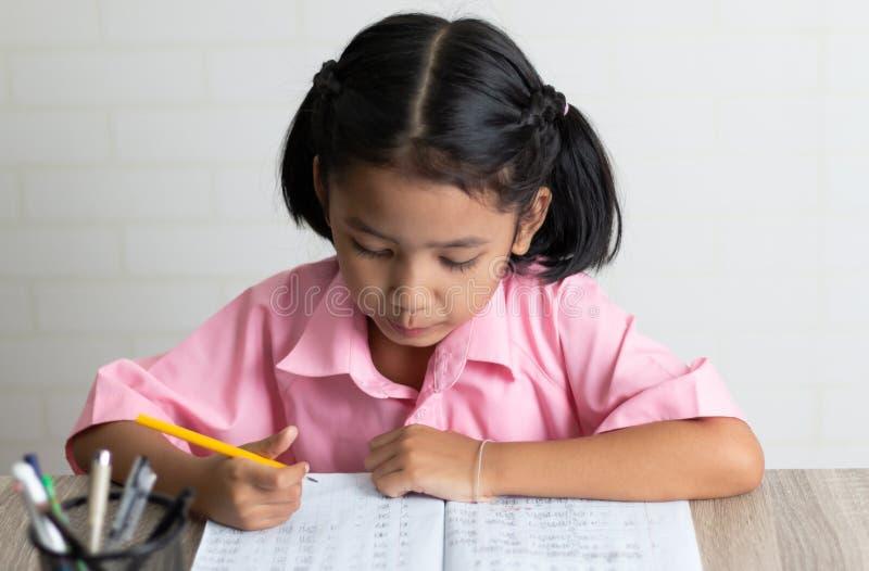 Uma menina está fazendo trabalhos de casa imagens de stock