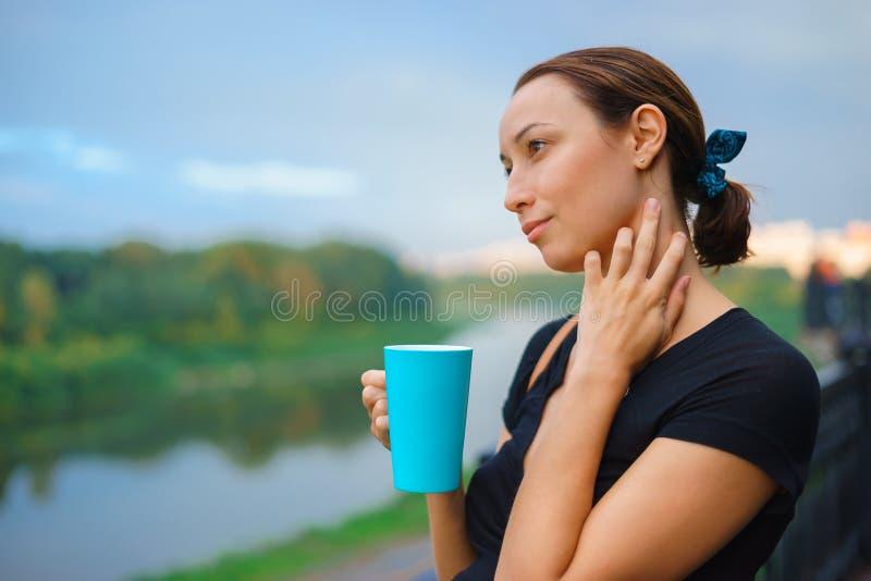Uma menina está fora com o copo do chá fotografia de stock royalty free