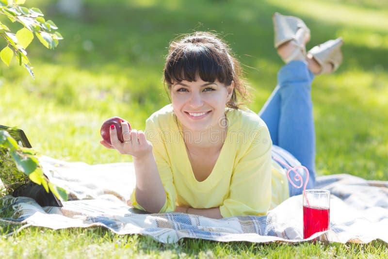Uma menina está guardando uma maçã que encontra-se na grama no parque foto de stock