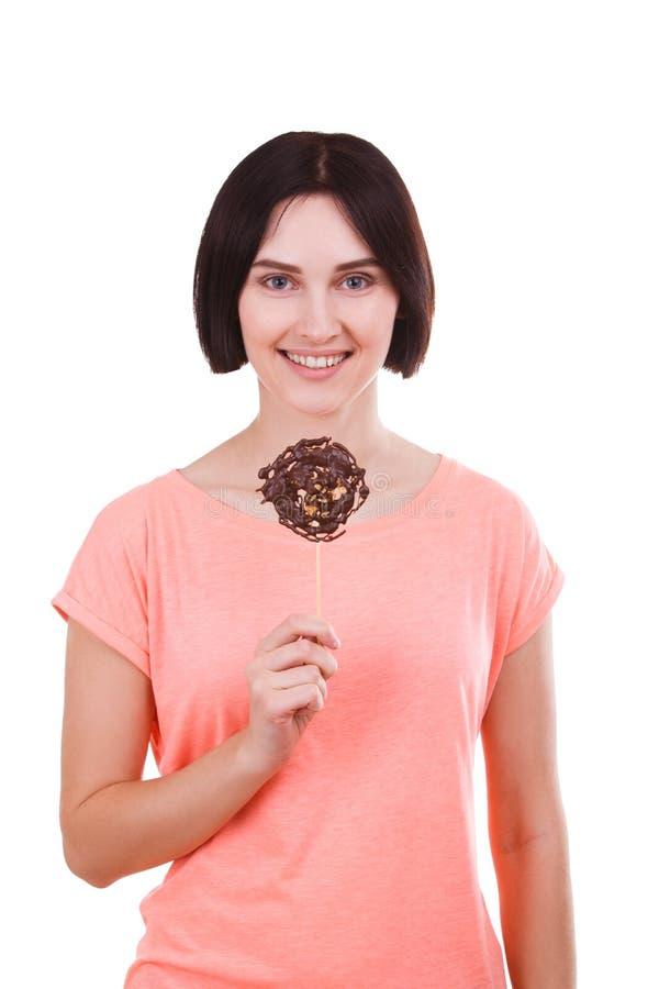 Uma menina está guardando um chocolate congelado em uma vara em um fundo branco fotos de stock