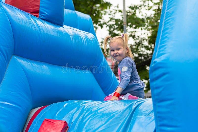 Uma menina está jogando em um parque de diversões imagem de stock