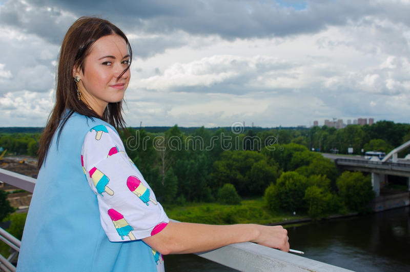 Uma menina está na ponte sobre o rio fotos de stock