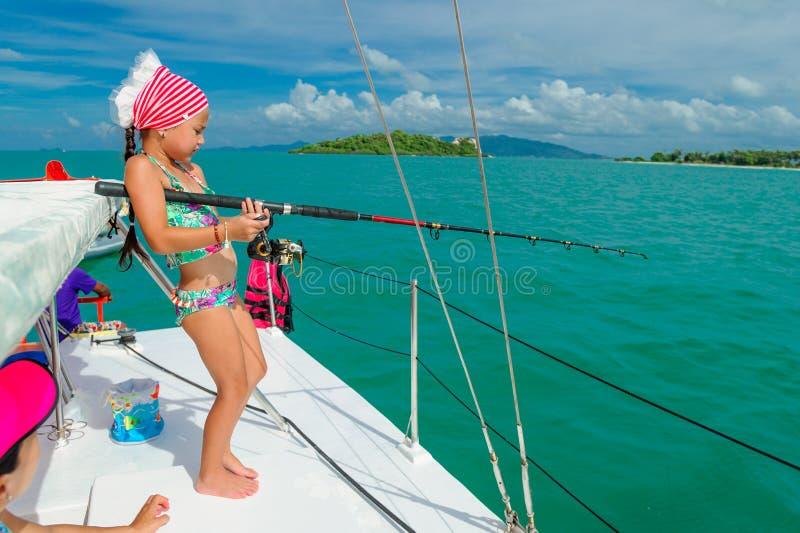 Uma menina está pescando em um barco Teste padrão tropical colorido ao redor foto de stock