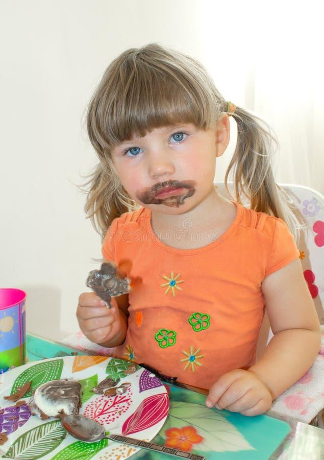 Uma menina está sentando-se em uma tabela e está comendo-se o gelado de chocolate Sua cara estava suja no chocolate fotografia de stock