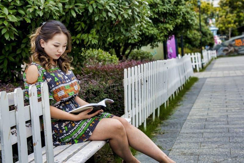 Uma menina está sentando-se em um livro do banco e de leitura em um parque imagens de stock royalty free