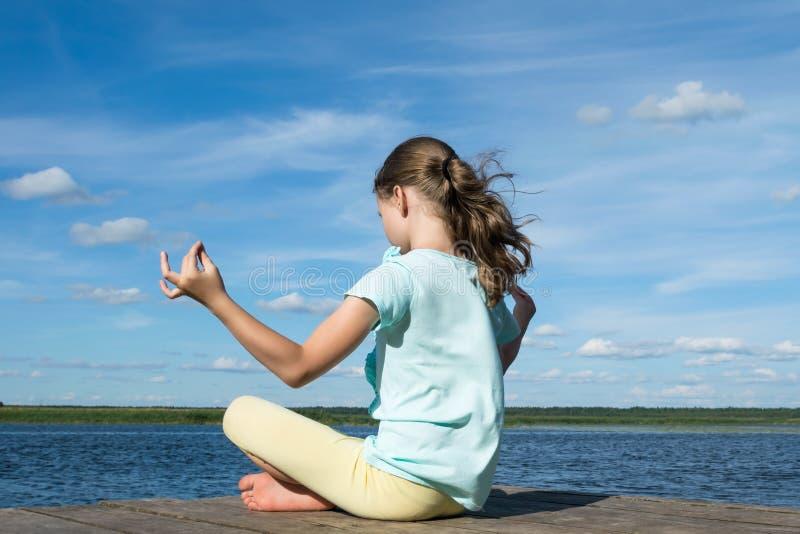 Uma menina está sentando-se na posição dos lótus sobre o cais pelo lago sobre o fundo de um céu azul bonito imagens de stock royalty free