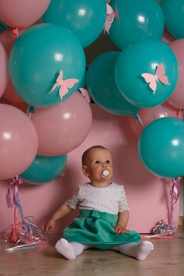 Uma menina está sentando-se no assoalho, em um fundo cor-de-rosa, perto dos balões, com uma chupeta celebration aniversário, um a fotografia de stock