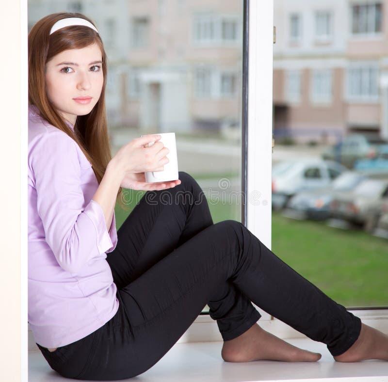 Uma menina está sentando-se no window-sill imagem de stock